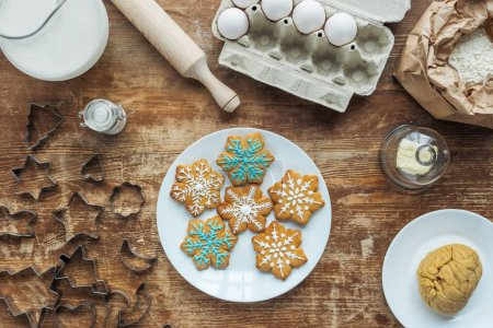Photo for Flat lay with Christmas cookies on plate, ingredients and cookie cutters arranged on wooden tabletop - Royalty Free Image