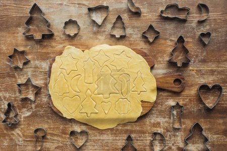 Photo for Top view of raw dough on cutting board and cookie cutters on wooden tabletop - Royalty Free Image