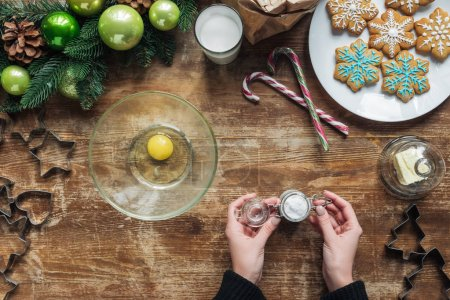 cropped shot of woman making dough for christmas cookies on wooden tabletop with decorative wreath