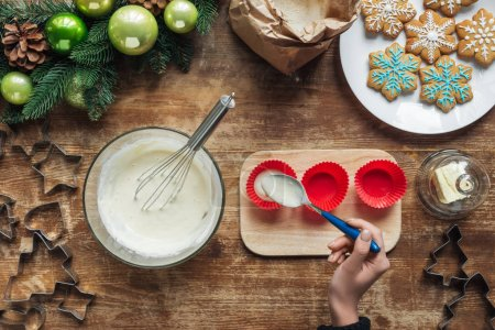 partial view of woman pouring dough into baking forms on wooden tabletop, christmas baking concept