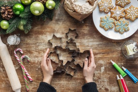 Photo for Partial view of woman holding cookie cutters on wooden tabletop with baked christmas cookies - Royalty Free Image