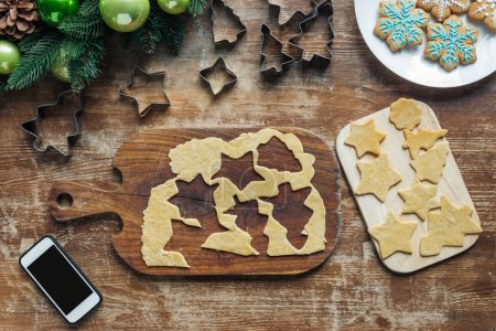 Photo for Top view of smartphone with blank screen, raw dough for christmas cookies and cookie cutters on wooden surface - Royalty Free Image