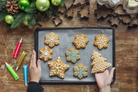 Photo for Partial view of woman holding baking pan with homemade christmas cookies on wooden surface - Royalty Free Image