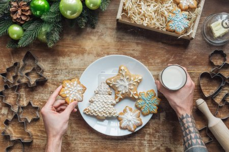 Photo for Cropped shot of man holding homemade christmas cookie and glass of milk on wooden surface - Royalty Free Image