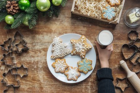 partial view of woman holding glass of milk on wooden tabletop with decorative christmas wreath, cookies and cardboard box