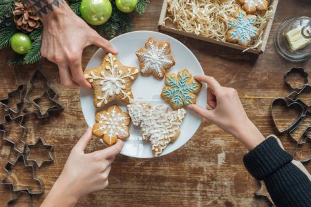 Photo for Cropped shot of friends holding homemade christmas cookies on plate on wooden surface - Royalty Free Image