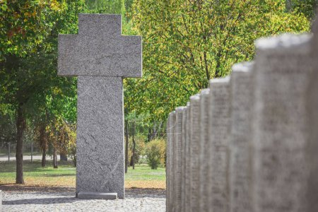 selective focus of old memorial monument in shape of cross at cemetery