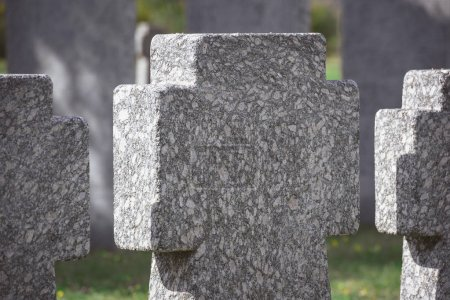 close up view of memorial stone crosses placed in row at graveyard