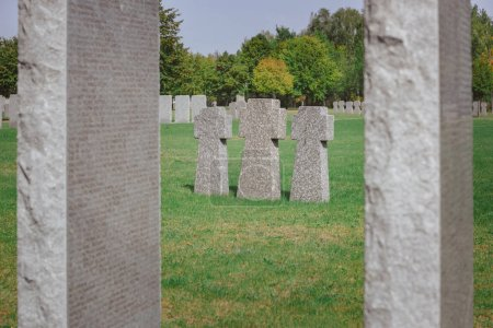 selective focus of identical memorial stone crosses placed in row at graveyard