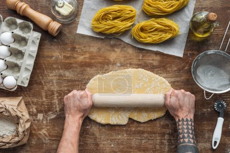 top view of male hands forming dough with rolling pin on wooden table