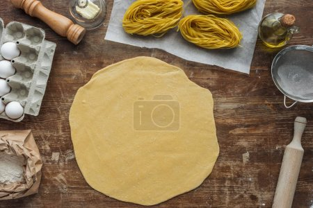 top view of rolled dough for pasta on wooden table