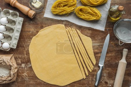 top view of cut raw dough for pasta on wooden table