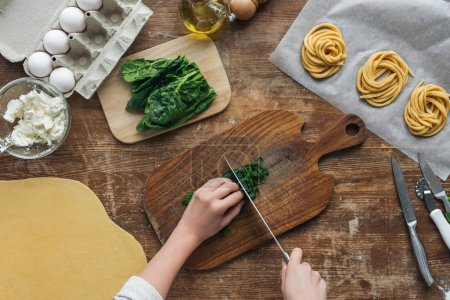 top view of female hands cutting spinach on wooden chopping board