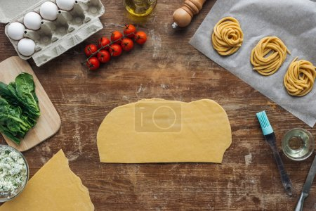 top view of cut raw dough pieces and pasta ingredients on wooden table