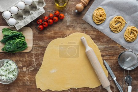 Photo for Top view of raw dough with rolling pin and pasta ingredients on wooden table - Royalty Free Image