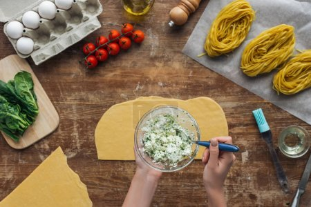 top view of female hands mixing spinach and creamy cheese with spoon in bowl on wooden table