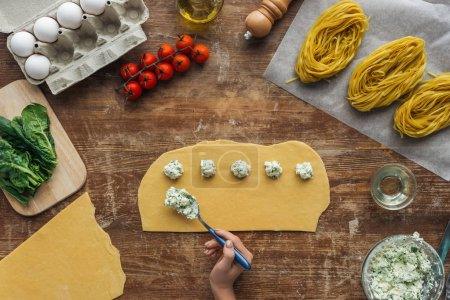 top view of female hands putting creamy cheese filling on dough for ravioli at wooden table