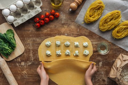 top view of female hands covering dough with filling for ravioli at wooden table