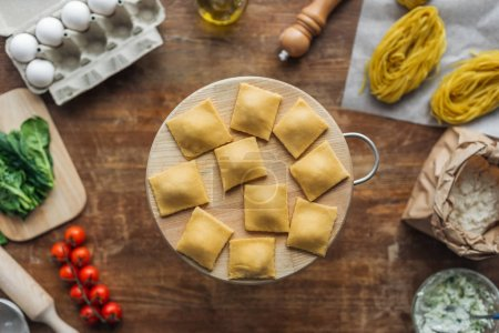 top view of raw ravioli on chopping board at wooden table