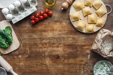 top view of raw ravioli on chopping board at wooden table with copy space