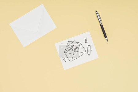Photo pour Carte blanche avec Merci lettrage collage d'emblée attiré enveloppe et plume isolée sur fond jaune - image libre de droit