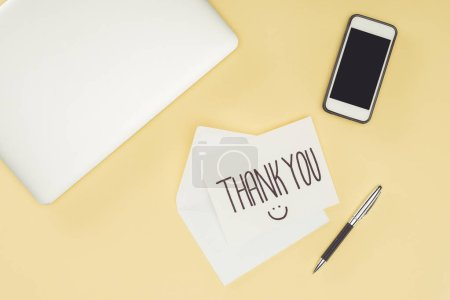 white postcard with thank you lettering, smartphone and laptop isolated on yellow background