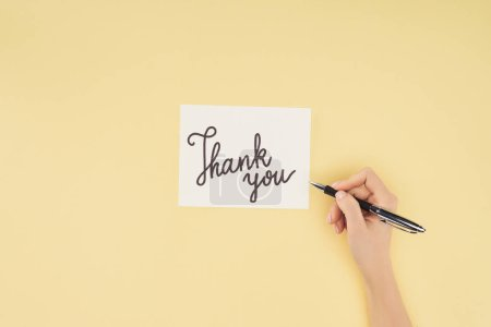 cropped person holding pen and white postcard with thank you lettering isolated on yellow background