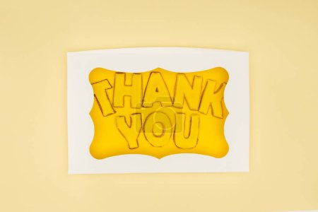 square-shaped cake in box with thank you lettering isolated on yellow background