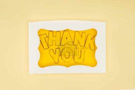 gâteau en forme de carré en boîte avec les lettres Merci isolé sur fond jaune