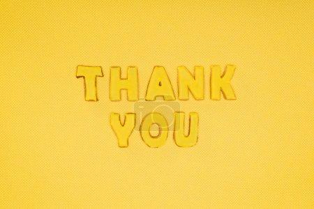 Photo pour Merci lettrage dans cookies isolé sur fond jaune - image libre de droit
