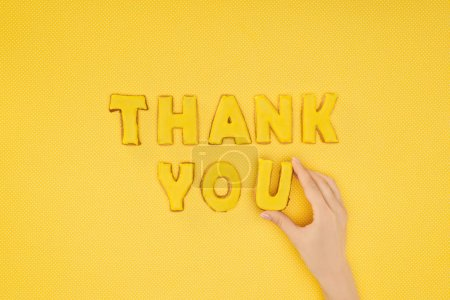 cropped view of hand adjusting thank you lettering in cookies isolated on yellow background