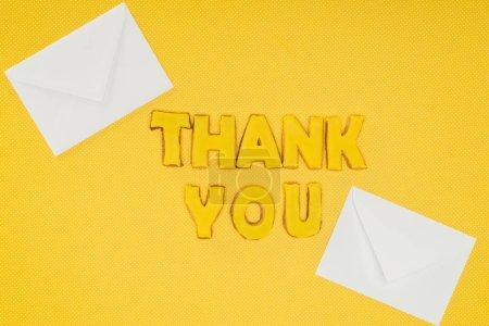 Photo pour Lettrage merci dans des cookies avec enveloppes blanches isolées sur fond jaune - image libre de droit