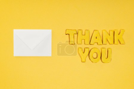 Photo for Thank you lettering in cookies with blank white envelope isolated on yellow background - Royalty Free Image