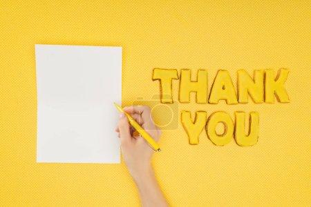 Photo pour Personne recadrée tenant stylo au-dessus de la feuille blanche et merci lettrage dans des cookies isolés sur fond jaune - image libre de droit