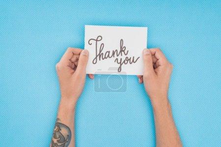 Photo pour Recadrée personne tenant le papier avec le lettrage Merci isolé sur fond bleu - image libre de droit