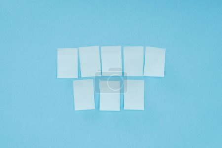 eight blank sticky notes isolated on blue background