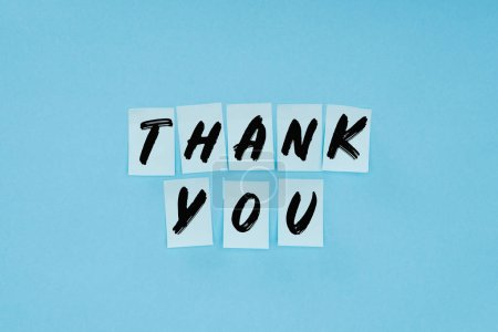 thank you wording on sticky notes isolated on blue background