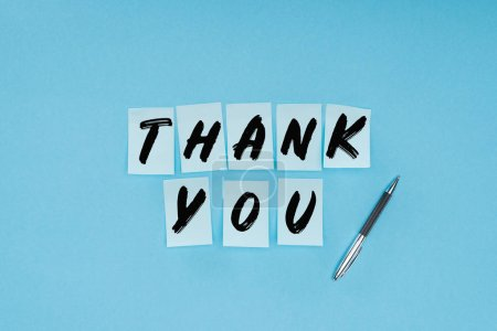 Photo for Thank you wording on sticky notes and pen isolated on blue background - Royalty Free Image