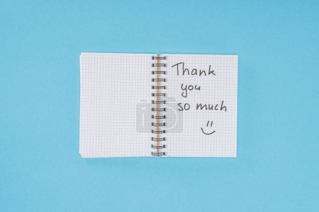 notebook with thank you so much lettering isolated on blue background