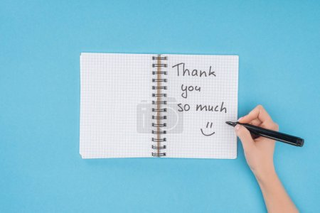 cropped person holding pen over notebook with thank you so much lettering isolated on blue background