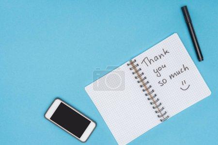 Photo pour Smartphone, stylo et ordinateur portable avec merci beaucoup lettrage isolé sur fond bleu - image libre de droit