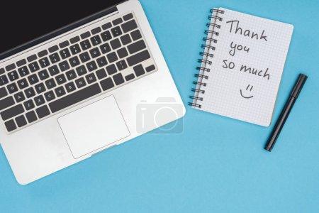 Photo pour Ordinateur portable, stylo et ordinateur portable avec merci beaucoup de lettrage isolé sur fond bleu - image libre de droit