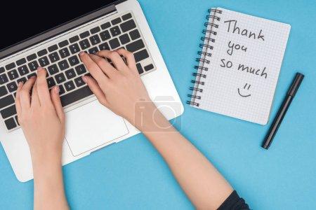 Photo pour Vue recadrée de la femme travaillant sur ordinateur et ordinateur portable avec merci beaucoup de lettrage isolé sur fond bleu - image libre de droit