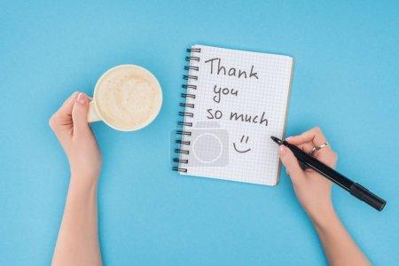 Photo pour Personne cultivée tenant stylo et tasse de café au-dessus du carnet avec merci beaucoup lettrage isolé sur fond bleu - image libre de droit