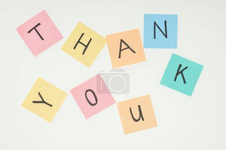colorful sticky notes spelling thank you on lace with clothespins isolated on white background