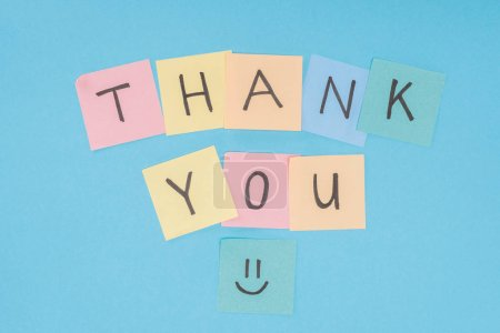 colorful sticky notes spelling thank you isolated on blue background