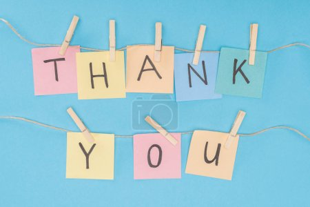 colorful sticky notes spelling thank you on lace with clothespins isolated on blue background