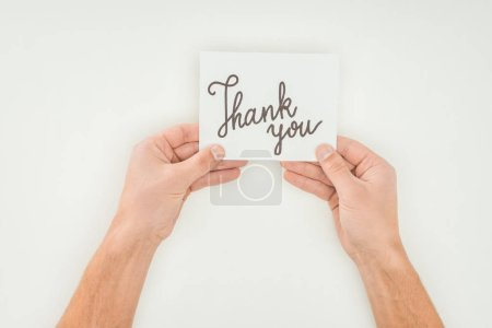 hands holding thank you lettering on white postcard isolated on white background