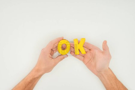 cropped person holding ok word in yellow cookies solated on white background