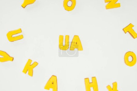 ua sign made of yellow cookies and scattered alphabet letters isolated on white background